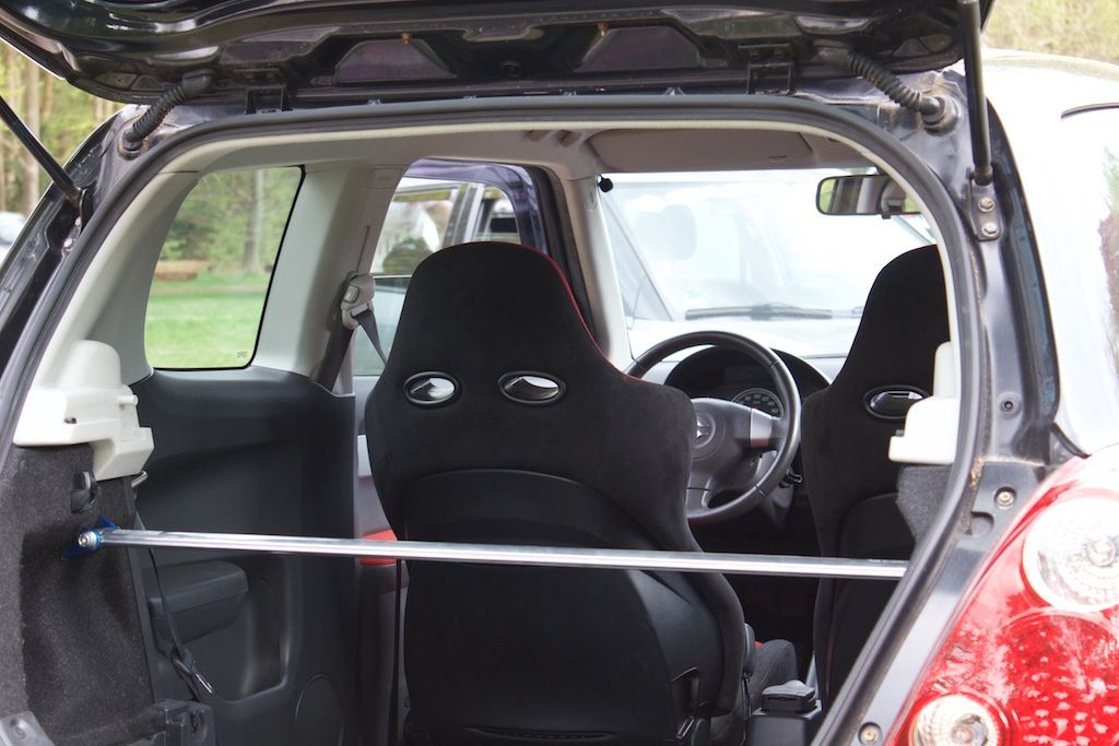 Photo of interior through open boot showing a strut brace and racing seats